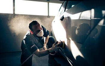 Maaco: Employee sanding vehicle